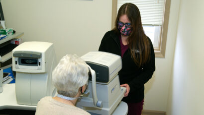 A doctor examines a patient's eyes through eye exam equipment.