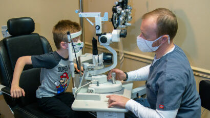 A doctor examines a young boy's eyes.