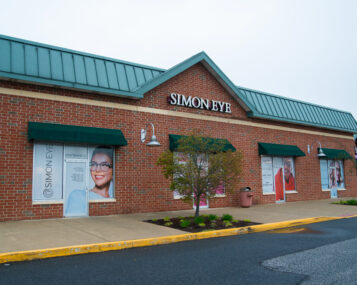 A brick building with Simon Eye in large green letters on the front store-face.