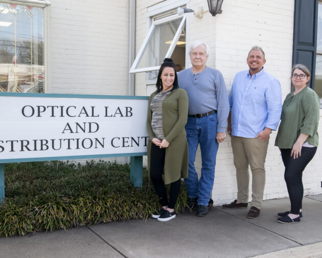 """Three people standing outside next to a sign that reads, """"Optical Lab and Distribution Center""""."""