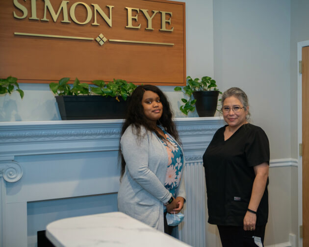 """Two people standing in front of a sign that reads, """"Simon Eye""""."""