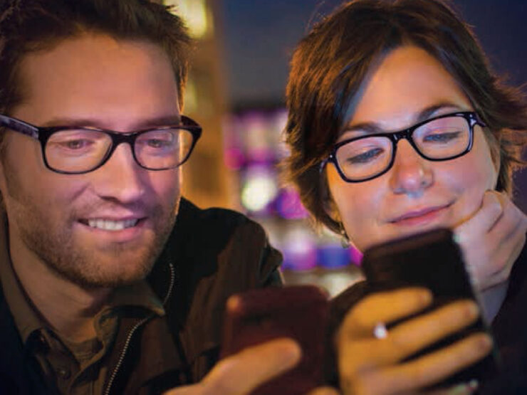 A man and woman, both wearing eyeglasses, look at their cellphones.