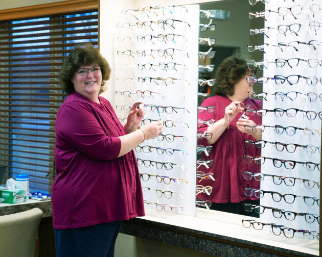 A person standing in front of a display of glasses.