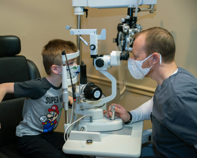 A young boy getting his eyes examined by a doctor.