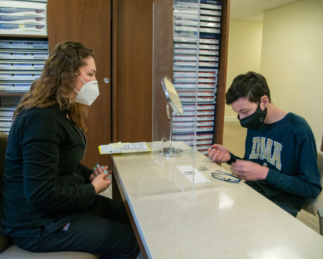A doctor watches a patient trying on contact lenses.
