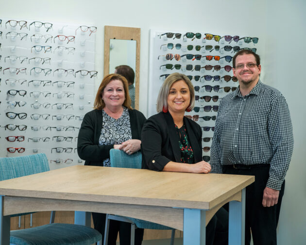 Three people in front of displays of glasses at Simon Eye Rehoboth.