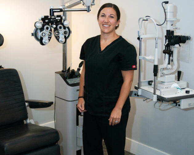 A woman in black scrubs stands in front of an eye examination machine.