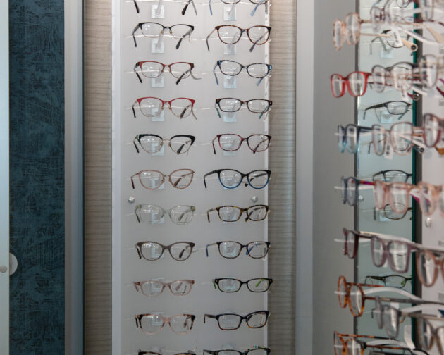 A tall panel of eyeglasses hanging on a white wall.