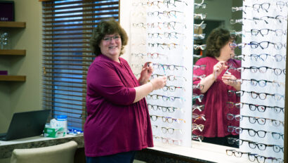 A woman in a purple shirt stands in front of a row of glasses.