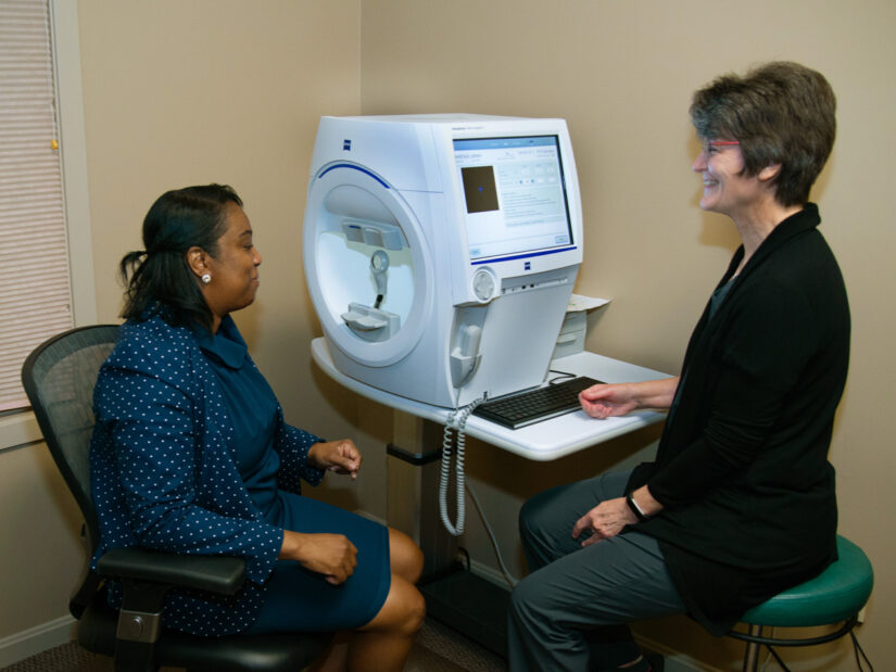 A patient and a doctor in front of eye exam equipment.