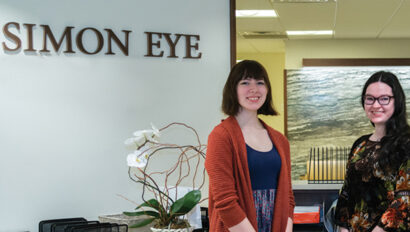 """Two women standing in front of a sign that reads, """"Simon Eye""""."""
