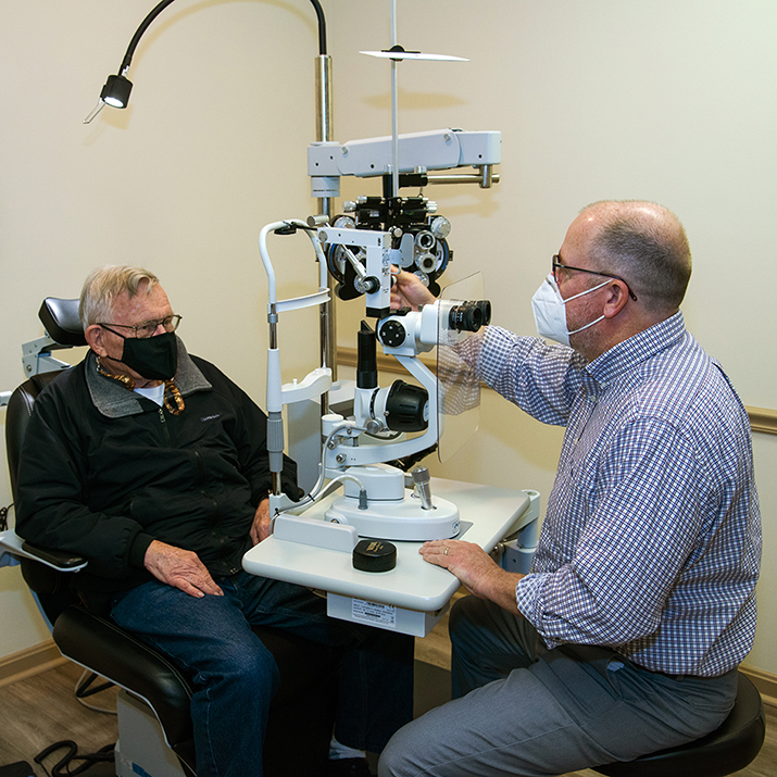 A doctor setting up eye exam equipment in front of a patient.