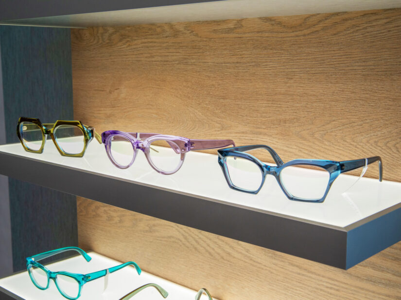 Three pairs of colorful glasses on display on a backlit shelf.