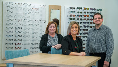 Three staff members of Simon Eye Rehoboth in front of glasses displayed on a wall.