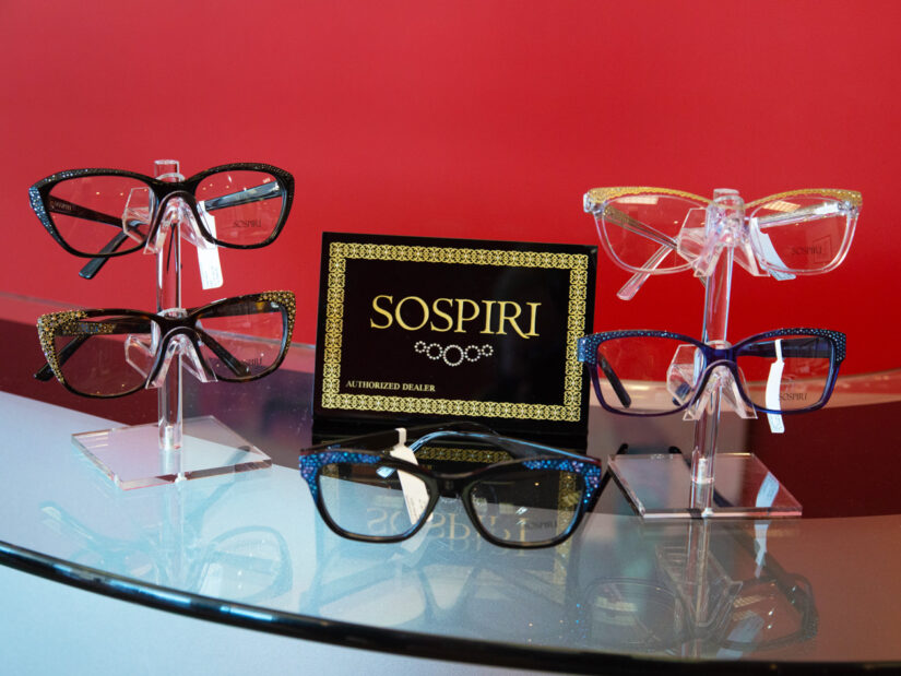 Five pairs of glasses on display along with a display of the Sospiri logo.