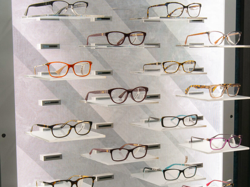 Glasses displayed in a backlit display case on a wall.