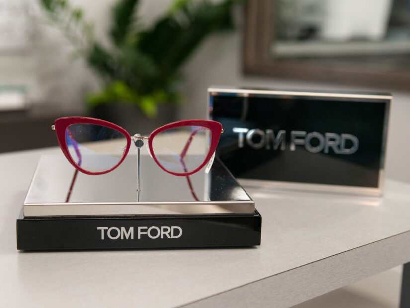 A pair of red glasses on display next to a display of the Tom Ford logo.