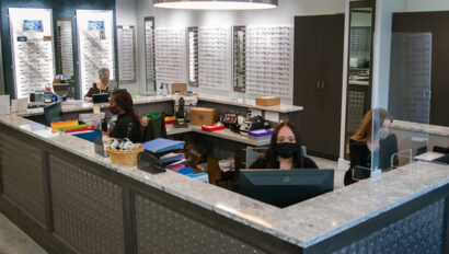 Three people working at the front desk of Simon Eye Wilmington.