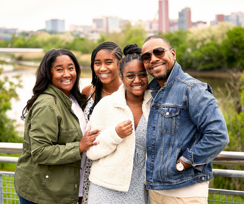 A family of four, one wearing eyeglasses and another wearing sunglasses, smiling together..